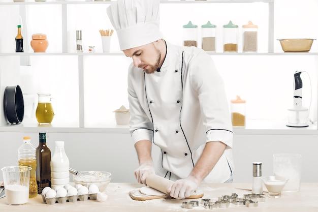 Chef de homem assando massa com rolo na cozinha