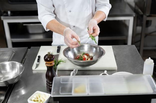 Chef de homem bonito preparando o prato com camarões na mesa da cozinha