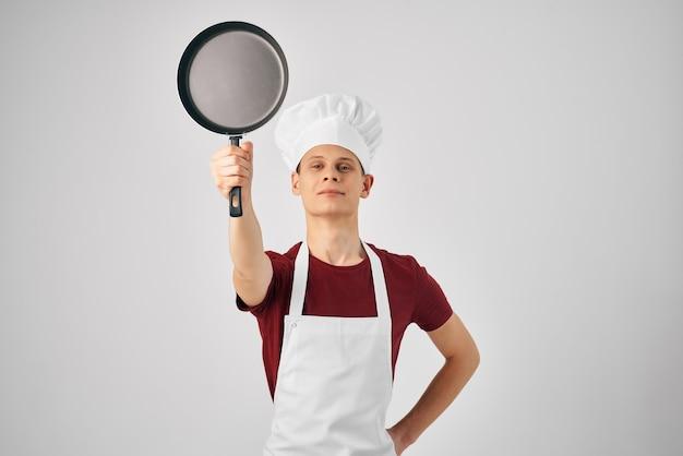 Chef de homem com uma tampa na cabeça, frigideira na mão, luz de fundo
