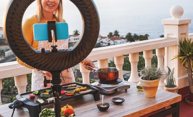 Chef de jovem mulher que cozinha ao ar livre durante o streaming on-line para a lição de masterclass de webinar em casa