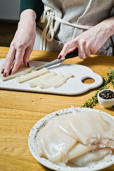 Chef de mãos corta lula crua em uma placa de corte