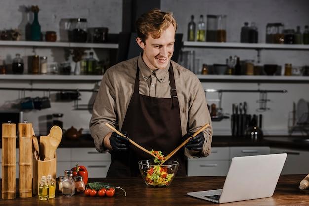 Chef de meia dose misturando ingredientes de salada olhando para um laptop