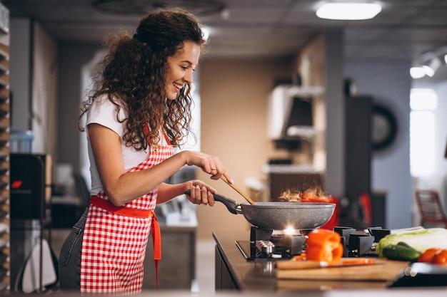 Chef de mulher cozinhar legumes na panela