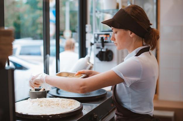 Chef de mulher de retrato assando panquecas em um uniforme de avental. serviço de fast food da cidade. o restaurante de fast food é uma pequena empresa.