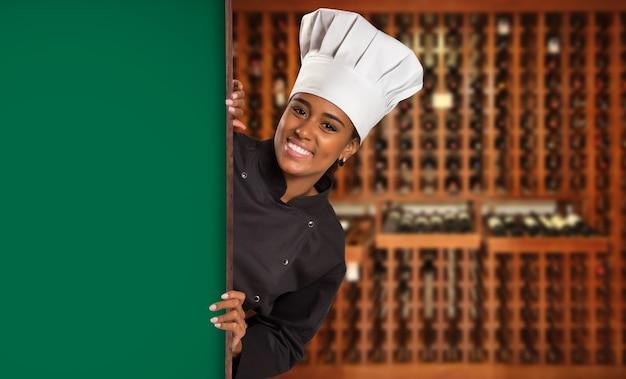 Chef de mulher negra brasileira cozinhando olhando para a câmera com placa verde no espaço borrado da casa de vinhos.