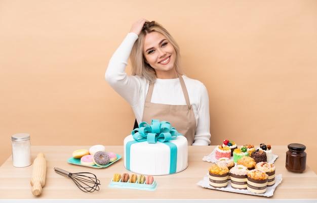 Chef de pastelaria adolescente com um bolo grande em uma mesa rindo