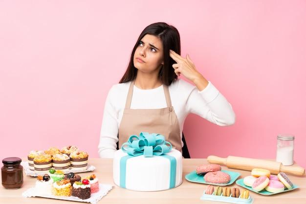 Chef de pastelaria com um bolo grande em uma mesa com problemas fazendo gesto de suicídio