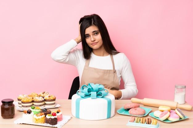 Chef de pastelaria com um bolo grande em uma mesa na parede rosa com uma expressão de frustração e não compreensão