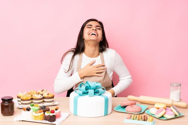 Chef de pastelaria com um bolo grande em uma mesa na parede rosa sorrindo muito