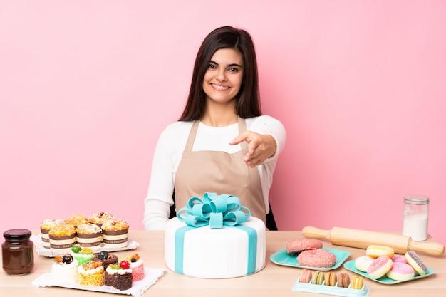 Chef de pastelaria com um bolo grande em uma mesa sobre parede rosa isolada, apertando as mãos para fechar um bom negócio