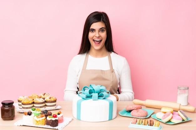Chef de pastelaria com um bolo grande em uma mesa sobre parede rosa isolada com expressão facial de surpresa