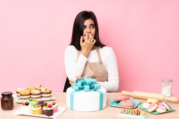 Chef de pastelaria com um bolo grande em uma mesa sobre parede rosa nervosa e assustada