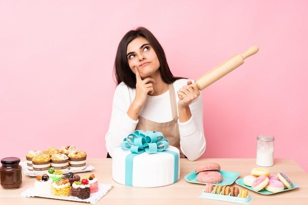 Chef de pastelaria com um bolo grande em uma tabela