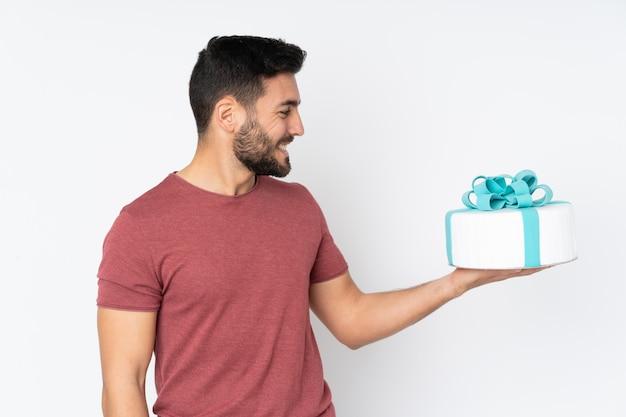 Chef de pastelaria com um bolo grande no branco com expressão feliz