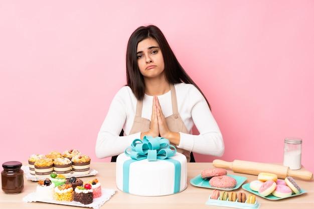 Chef de pastelaria com um grande bolo em uma mesa na parede rosa mantém a palma da mão