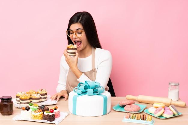 Chef de pastelaria com um grande bolo em uma mesa na parede rosa