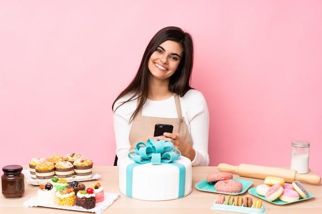 Chef de pastelaria com um grande bolo em uma mesa sobre parede rosa isolada, enviando uma mensagem com o celular