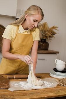Chef de pastelaria de mulher ou padeiro ou dona de casa amassa a massa na cozinha. publicidade de produtos caseiros