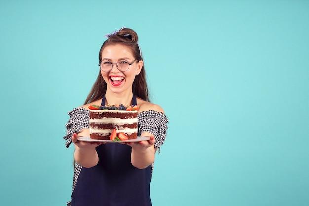 Chef de pastelaria feliz posando para a câmera com um bolo nas mãos