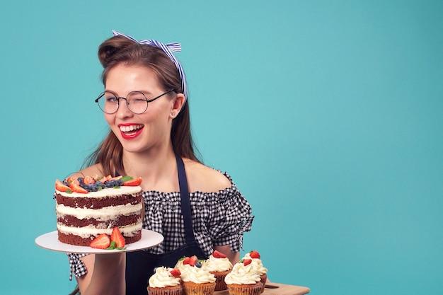 Chef de pastelaria morena emocional segurando um bolo na palma da mão e sorrindo para a câmera no estúdio