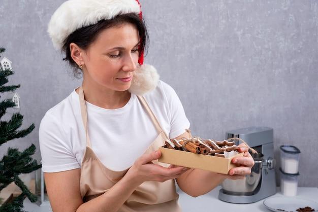 Chef de pastelaria mulher com chapéu de natal, segurando a caixa com produtos assados de natal.