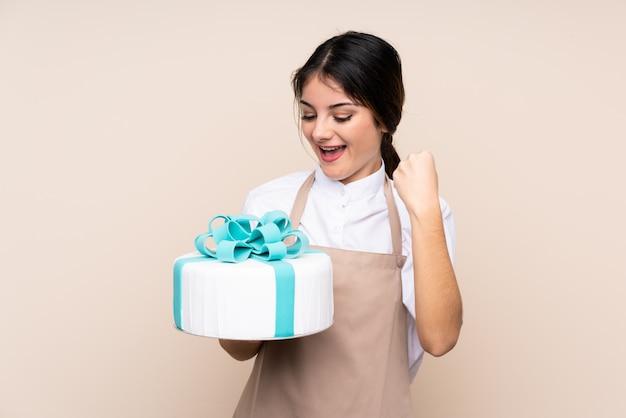 Chef de pastelaria mulher segurando um bolo grande sobre parede isolada comemorando uma vitória