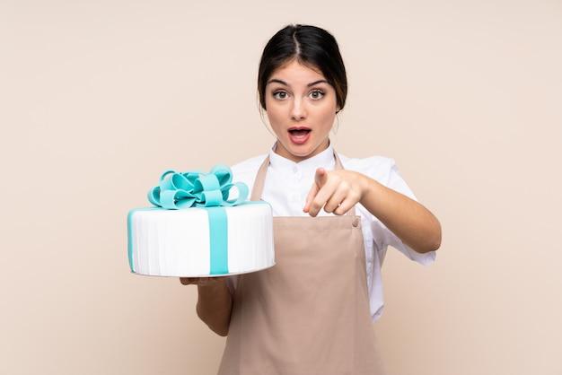 Chef de pastelaria mulher segurando um bolo grande surpreso e apontando a frente