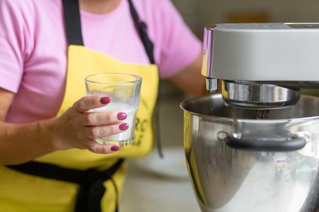 Chef de pastelaria profissional de mulher preparando uma sobremesa. adiciona ingredientes e mistura a massa em uma batedeira