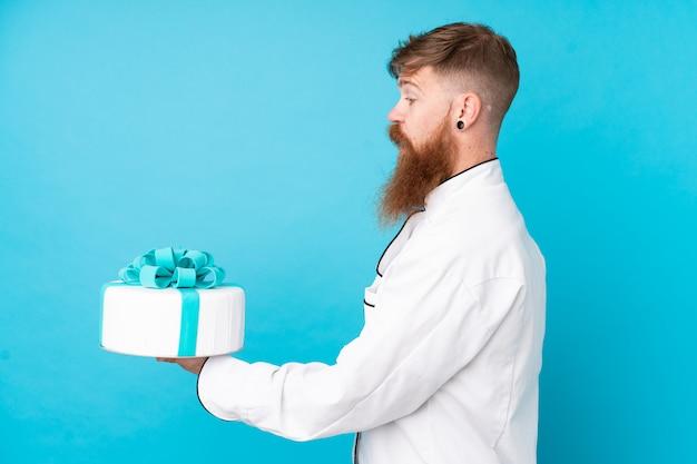 Chef de pastelaria ruiva com barba longa, segurando um bolo grande sobre parede azul isolada com expressão feliz