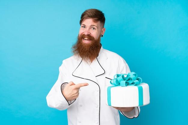 Chef de pastelaria ruiva com barba longa, segurando um bolo grande sobre parede azul isolada e apontando-o