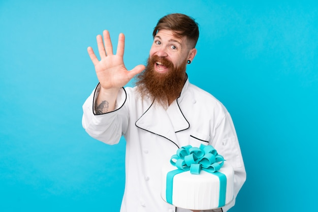 Chef de pastelaria ruiva com barba longa, segurando um bolo grande sobre parede azul isolada, saudando com a mão com expressão feliz