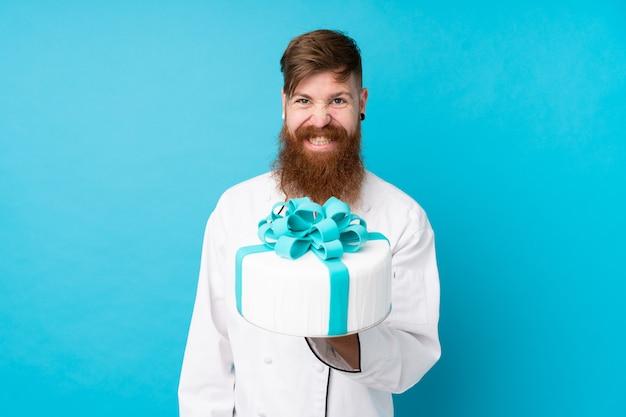 Chef de pastelaria ruiva com barba longa, segurando um bolo grande sobre parede azul isolada