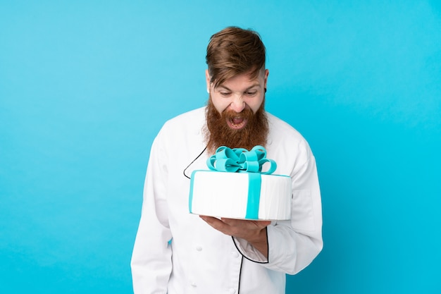 Chef de pastelaria ruiva com barba longa, segurando um bolo grande sobre parede azul