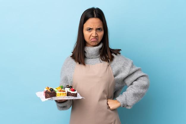 Chef de pastelaria segurando um bolo grande sobre azul isolado com expressão infeliz.