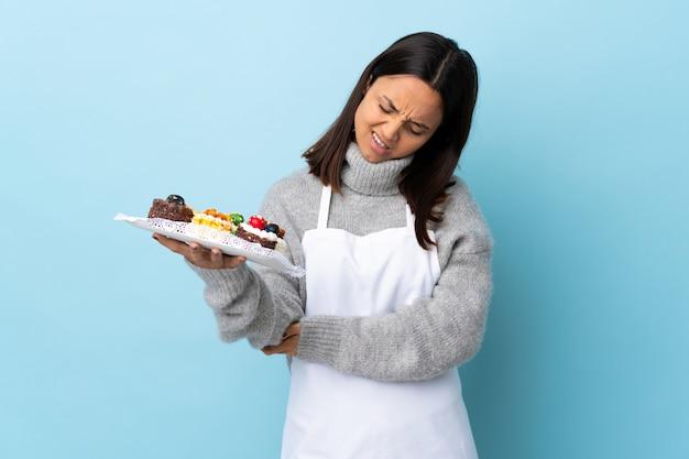 Chef de pastelaria segurando um bolo grande sobre parede azul com dor no cotovelo.