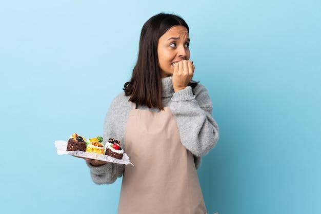 Chef de pastelaria segurando um bolo grande sobre parede azul, nervoso e assustado, colocando as mãos na boca