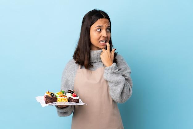Chef de pastelaria segurando um bolo grande sobre parede azul, nervoso e assustado