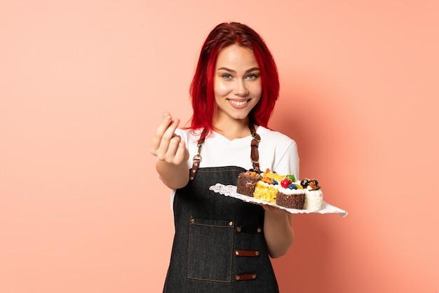 Chef de pastelaria segurando um muffins isolado na parede rosa, fazendo dinheiro gesto