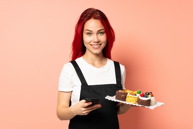 Chef de pastelaria segurando um muffins isolado no fundo rosa, enviando uma mensagem com o celular