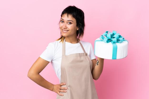 Chef de pastelaria uruguaio segurando um bolo grande sobre parede rosa aplaudindo