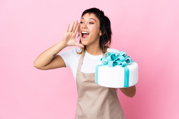 Chef de pastelaria uruguaio segurando um bolo grande sobre parede rosa gritando com a boca aberta