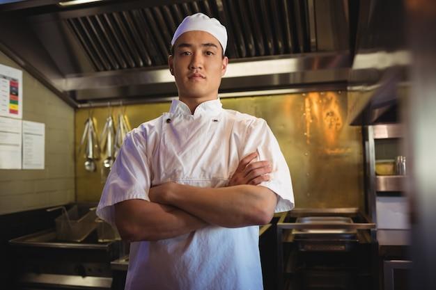 Chef de pé com os braços cruzados na cozinha comercial