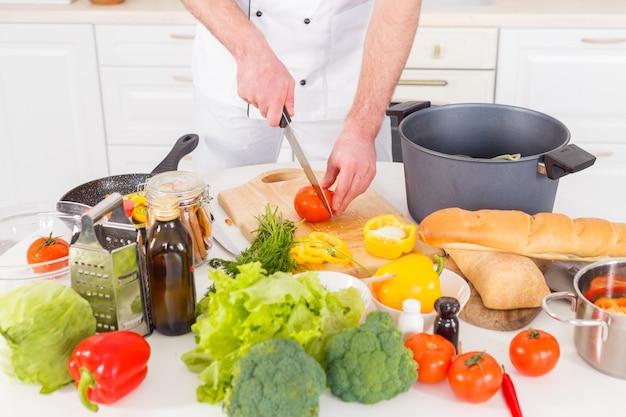 Chef de pé com uma faca e cozinhar um vegetariano legumes frescos