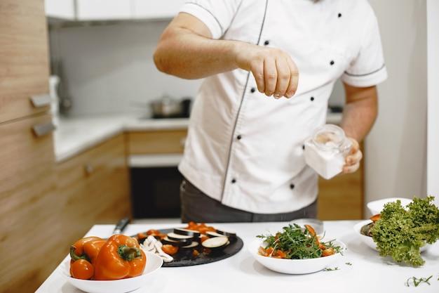 Chef de pé na cozinha de casa, cozinhando