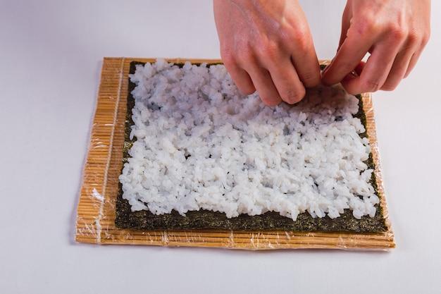 Chef de sushi mulher fazendo um rolo maki com algas marinhas e arroz japonês - processo de preparação.