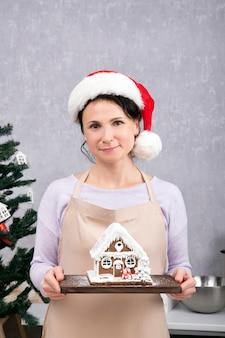 Chef de uma linda mulher com chapéu de papai noel tem casa de pão de mel nas mãos dela. quadro vertical.