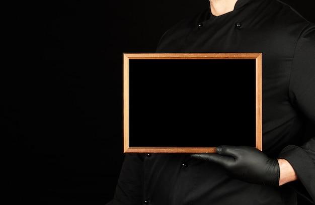 Chef de uniforme preto e luvas de látex preto mantém um quadro de madeira vazio