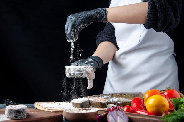 Chef de visão frontal cobrindo peixe cru com farinha de vegetais frescos em uma tigela de farinha de tábua de madeira na mesa da cozinha