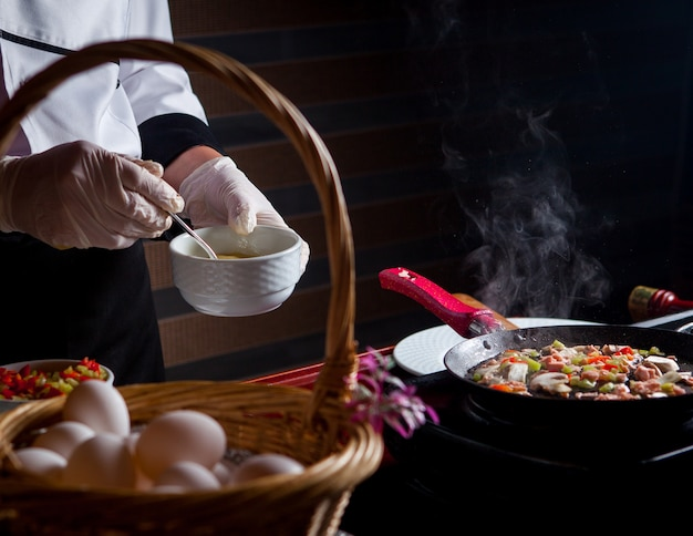 Chef de vista lateral preparando deliciosa refeição na cozinha.