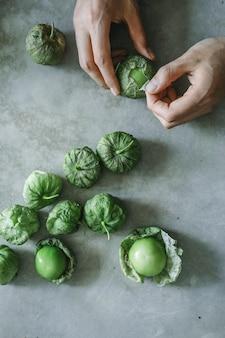 Chef descascando tomatillos verdes frescos